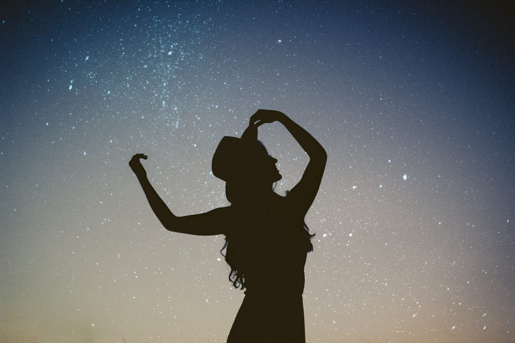 woman dancing under the stars to ground herself