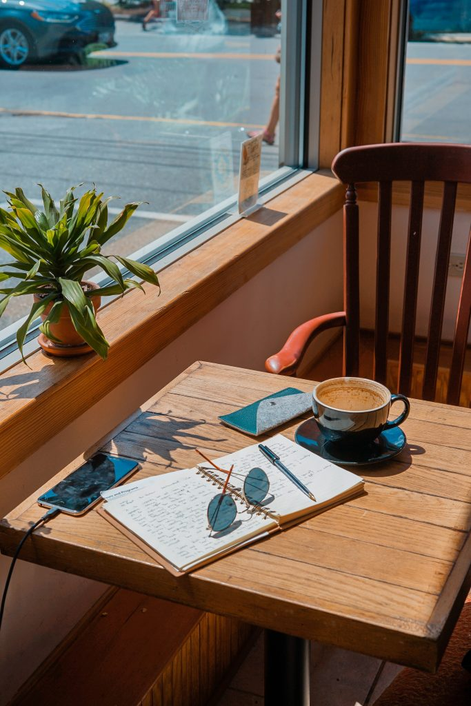 journal on table with coffee near window with plant on window ledge