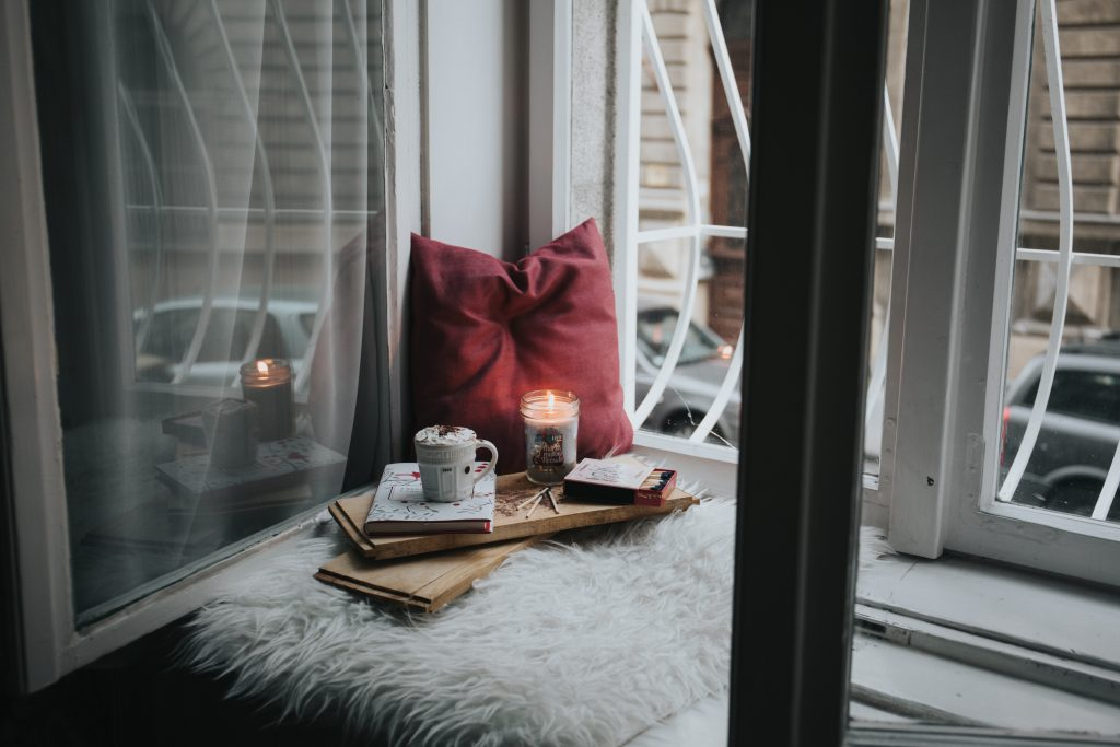 open window with a candle burning, a red pillow and cup of coffee