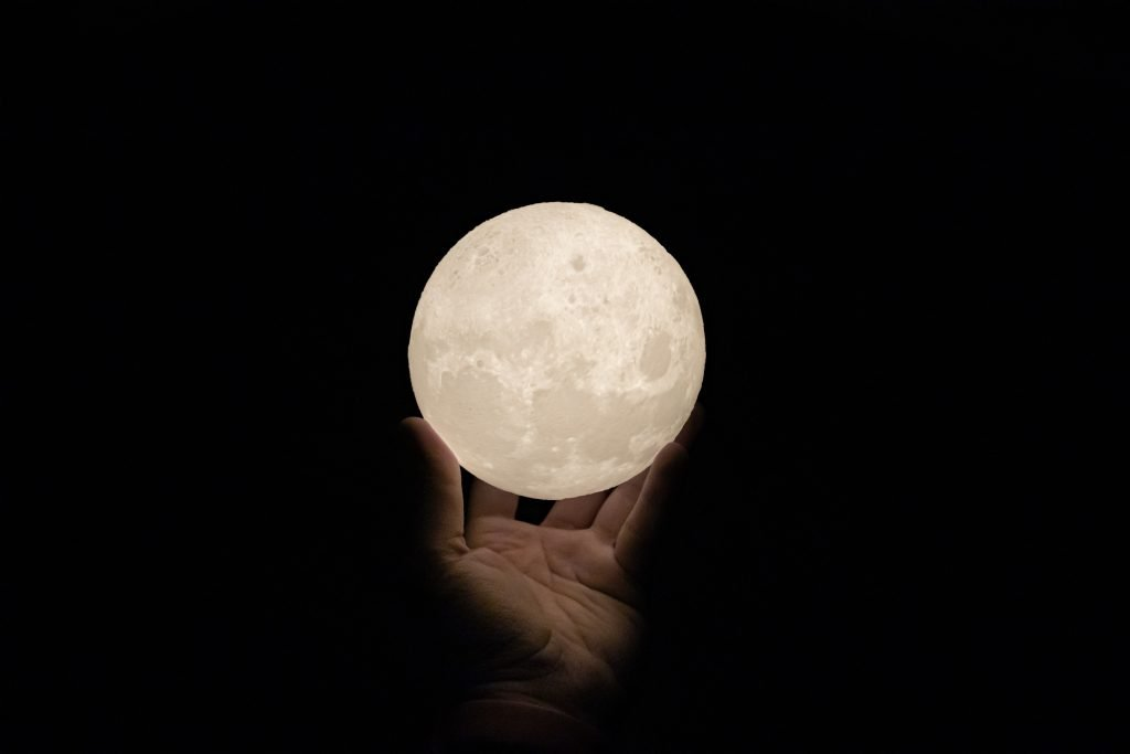 black background with a hand holding a glowing white moon. full moon ritual
