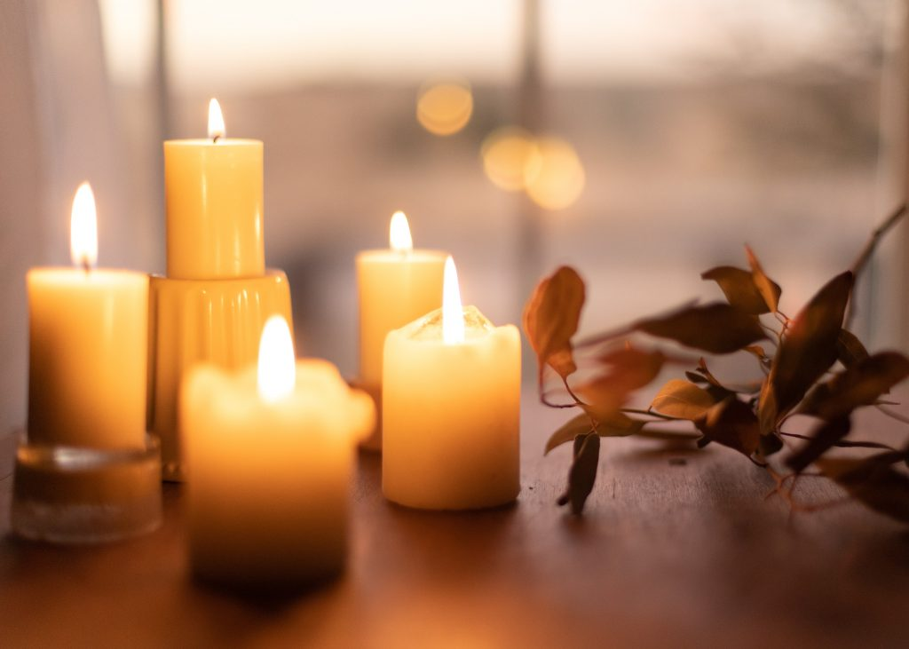 5 warm hued white candles with a leaf next to it on a wooden table surface