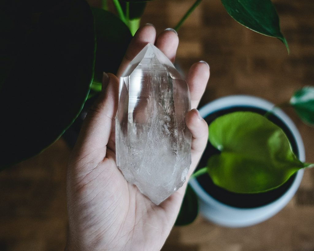 clear quartz crystal with green plant in the background used for a post about affirmations for manifesting