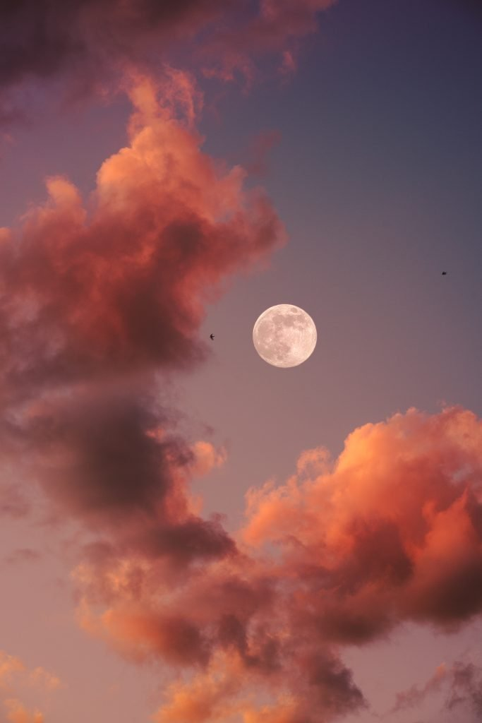 full moon in a pinkish sky surrounded by a few clouds