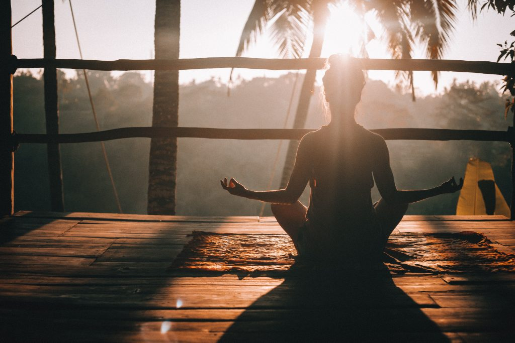 woman sitting facing cross legged on a wooden deck facing the sunrise and palm leaves