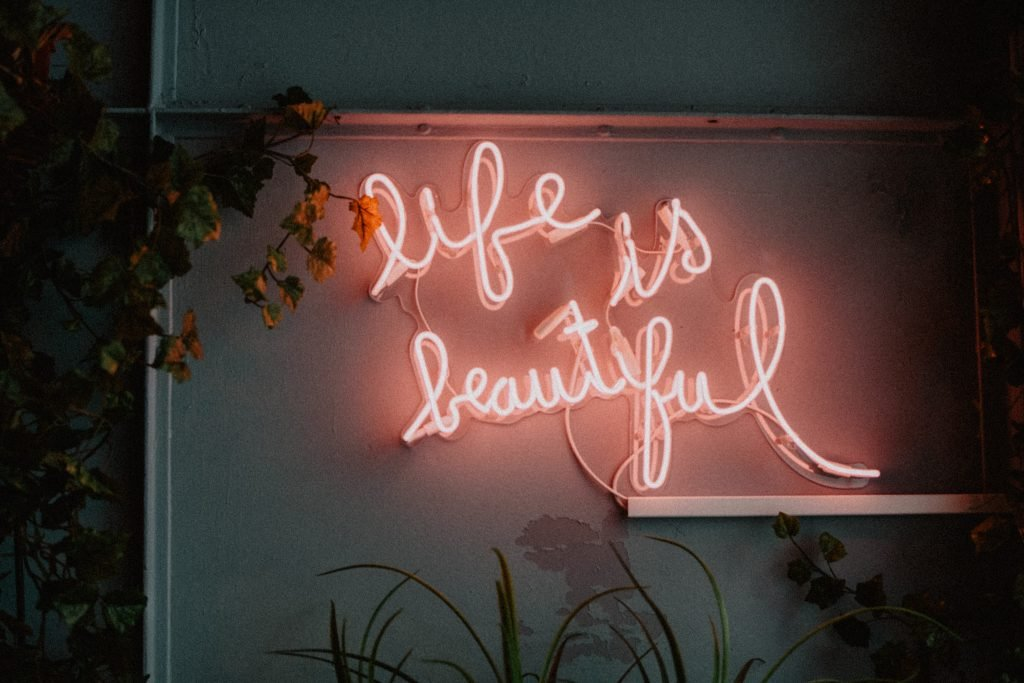 """neon sign that reads """"life is beautiful"""" on a wall with plants surrounding, used for the post affirmations for manifesting"""