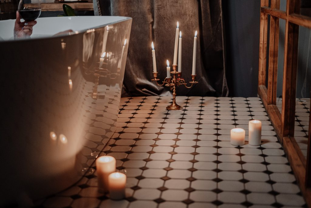 checkered floor with candles spread out next to a white bath tub