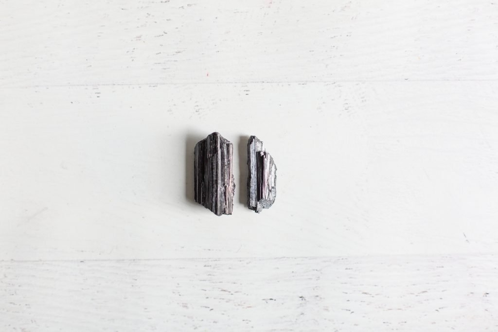 white background with two black tourmaline stones on it