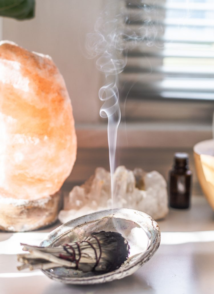 spiritual awakening picture shows a bundle of sage burning and a salt lamp and crystal in background