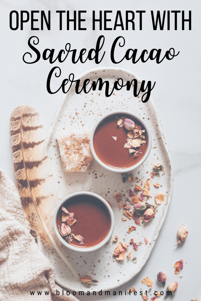 text reads open the heart with sacred cacao ceremony and background image is of two mugs of cacao with a feather, crystal and rose buds around it