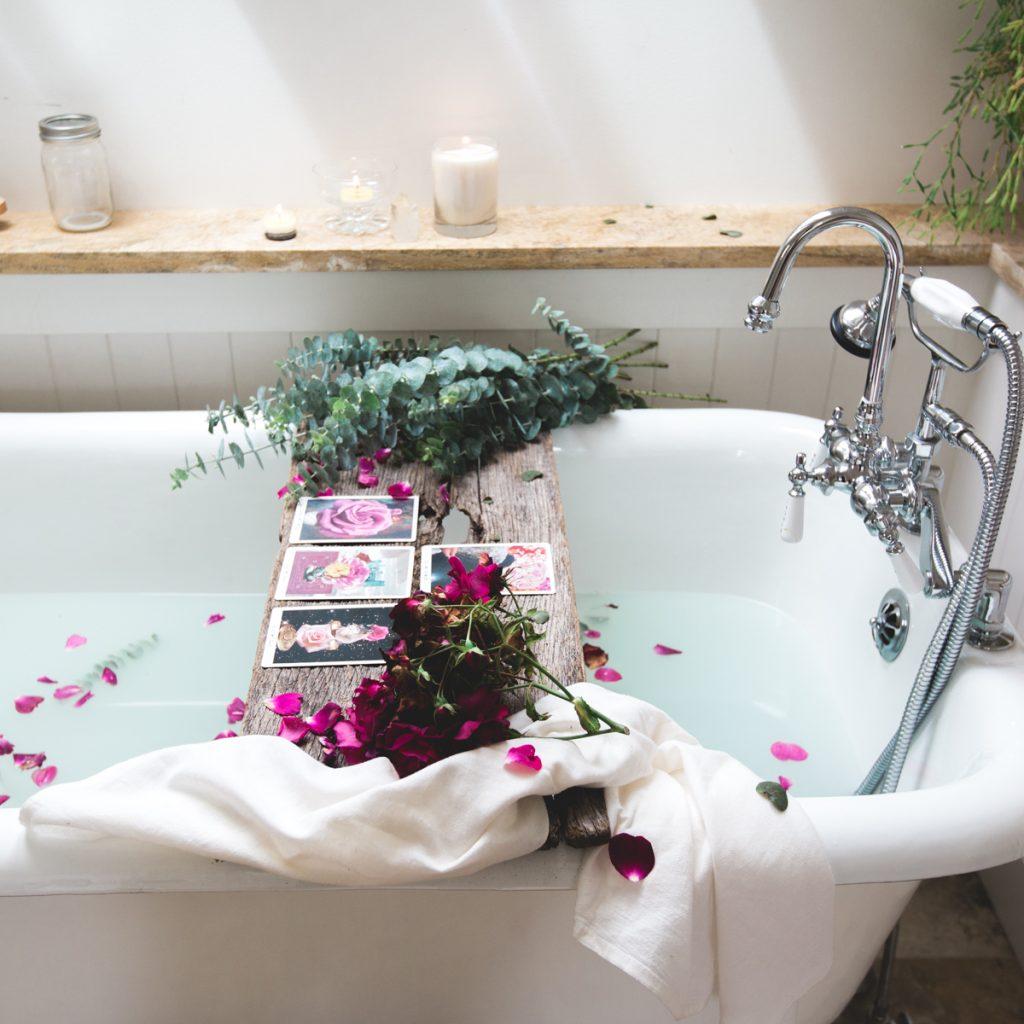 spiritual awakening picture of a bath with tarot cards flowers and eucalyptus