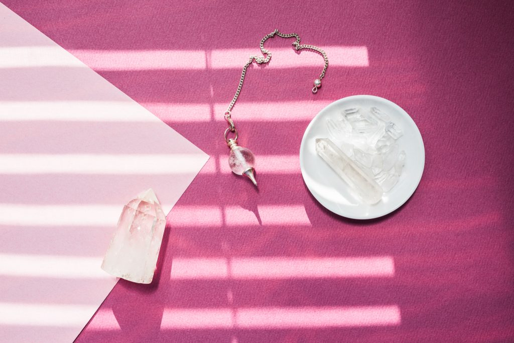 pendulum and clear quartz crystals with pink background for how to strengthen your intuition